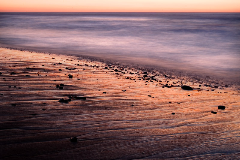sea and wet sand at dusk
